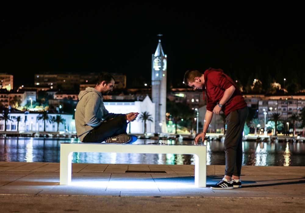 Vue en de nuit des jeunes avec un banc urbain connecté modèle stéora