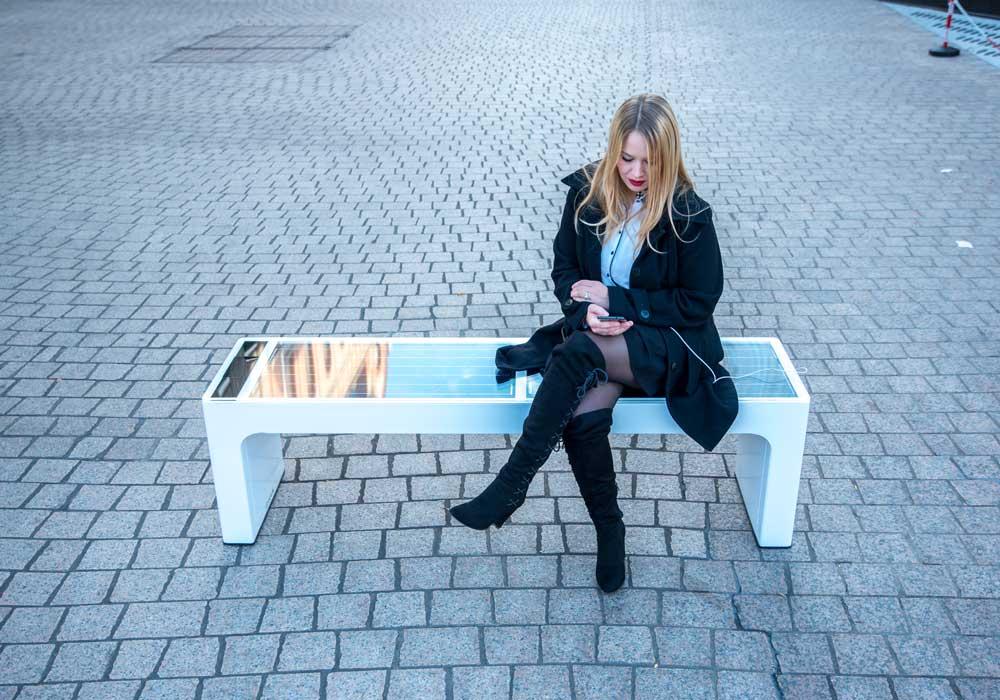 Vue en plein jour d'une femme assises sur un banc urbain connecté modèle stéora